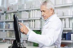 Pharmacien masculin Touching Monitor Screen dans la pharmacie photos stock