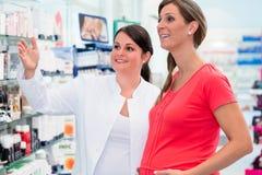 Pharmacien montrant des drogues de femme enceinte dans la pharmacie Photographie stock libre de droits