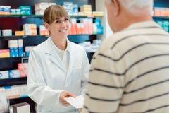 Pharmacien prenant le glissement de prescription de l'homme supérieur images libres de droits