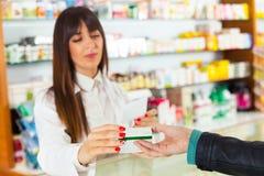Pharmacien proposant la drogue médicale à l'acheteur dans la pharmacie photographie stock