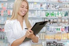 Pharmacien rendant compte le produit dans la pharmacie photos libres de droits