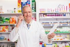 Pharmacien supérieur de sourire au téléphone Images libres de droits