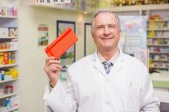 Pharmacien supérieur de sourire montrant l'enveloppe Photos libres de droits