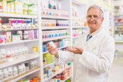 Pharmacien supérieur de sourire montrant le médicament images libres de droits