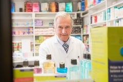 Pharmacien supérieur de sourire se tenant derrière une étagère Image stock