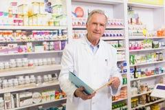 Pharmacien supérieur de sourire tenant des carnets Photo stock