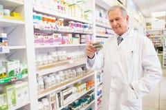 Pharmacien supérieur de sourire tenant la boursouflure Photographie stock libre de droits