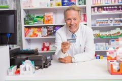 Pharmacien supérieur de sourire tenant la carte de crédit Image stock