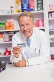 Pharmacien supérieur de sourire tenant la carte de crédit Photographie stock