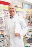 Pharmacien supérieur de sourire tenant le presse-papiers Images libres de droits