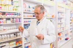 Pharmacien supérieur regardant la médecine et la prescription Photos stock