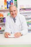 Pharmacien supérieur se penchant sur la contre- prescription se tenante Photos stock