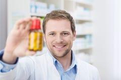Pharmacien supportant une bouteille de comprimés Images libres de droits