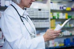 Pharmacien tenant le comprimé numérique tout en vérifiant la médecine photos stock