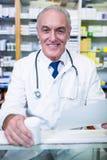Pharmacien tenant une prescription et une médecine photographie stock libre de droits