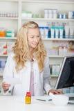 Pharmacien Using Computer While tenant le papier de prescription photos stock