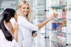 pharmaciens à l'aide des dispositifs numériques et se souriant photographie stock libre de droits