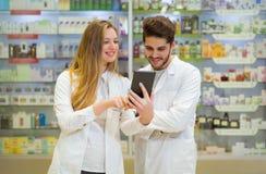 Pharmaciens à l'aide du comprimé numérique photos stock
