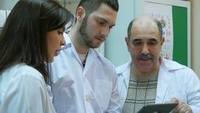 Pharmaciens à l'aide du comprimé numérique tout en vérifiant la médecine dans la pharmacie photos stock