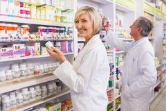 Pharmaciens dans le manteau de laboratoire regardant la médecine Photographie stock