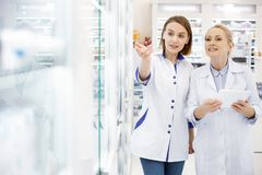 Pharmaciens féminins réfléchis étudiant l'étalage Image stock