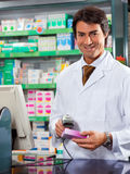 Pharmacist. Portrait of mid adult pharmacist scanning medicine with barcode reader