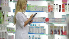 Pharmacist accounting the product in drugstore stock video