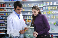 Pharmacist advising client at pharmacy. How to take medicine Royalty Free Stock Image