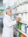 Pharmacist Arranging Medicines On Shelf Royalty Free Stock Image