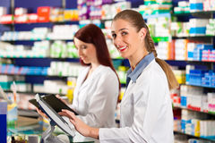 Pharmacist with assistant in pharmacy Stock Photos