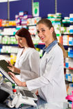 Pharmacist with assistant in pharmacy Royalty Free Stock Photography
