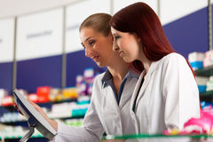 Pharmacist with assistant in pharmacy Stock Image