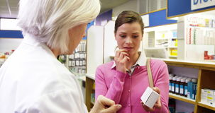 Pharmacist assisting the bottle of drug to customer stock footage
