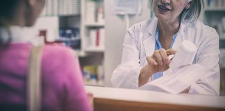 Pharmacist assisting the bottle of drug to customer royalty free stock images
