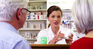 Pharmacist assisting the bottle of drug to customers