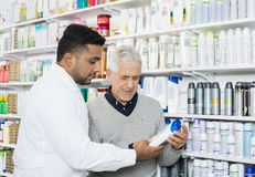 Pharmacist Assisting Customer In Buying Product. Young pharmacist assisting senior male customer in buying product at pharmacy Stock Photos