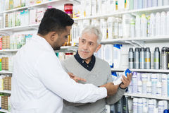 Pharmacist Assisting Senior Customer In Buying Product Royalty Free Stock Photos