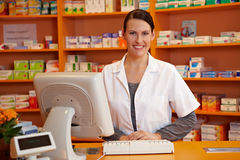 Pharmacist behind checkout counter Royalty Free Stock Photography