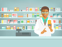 Pharmacist black man with medicine at counter in pharmacy. Pharmacist at counter in pharmacy. Black man druggist stands opposite shelves with medicines and Stock Images