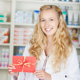 Pharmacist With Bonus Coupon Card Gift. Female young blond pharmacist holding bonus coupon card gift in pharmacy royalty free stock photo