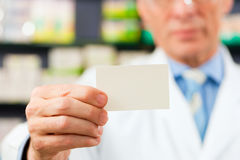 Pharmacist with business card in pharmacy. Focus on card Stock Images