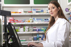 Pharmacist at the cash desk. Female friendly pharmacist at the cash desk computer looks at the camera Stock Photos