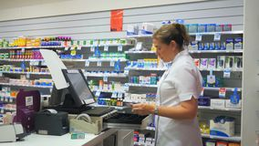 Pharmacist at a cash register in a pharmacy. A pharmacist processes a transaction at a cash register in an australian pharmacy stock video