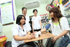 Pharmacist checking blood pressure for her patient Stock Images