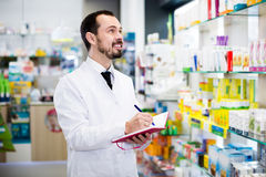 Pharmacist checking drugs in pharmacy Stock Photography