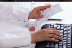 Pharmacist checking information about medicines. Pharmacist's hands checking information about medicines Stock Photos