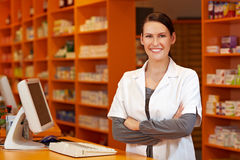 Pharmacist at checkout. Happy pharmacist with her arms crossed at checkout in pharmacy royalty free stock images