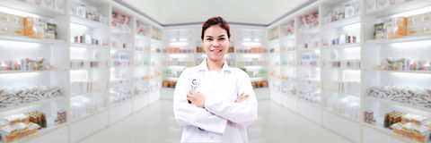 Pharmacist chemist and medical doctor woman asia with stethoscop. E and clipboard checking medicine cabinet and pharmacy drugstore Royalty Free Stock Images
