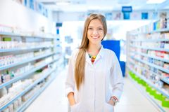 Pharmacist chemist woman standing in pharmacy. Drugstore