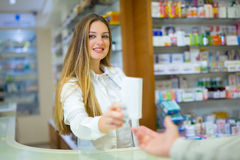 Pharmacist and Client in a Drugstore. Smiling royalty free stock photography